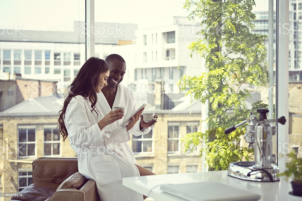 Couple in the morning Afro american man and beautiful brunette wearing white bathrobes drinking coffee and using a digital tablet together in the morning in their apartment. 30-39 Years Stock Photo