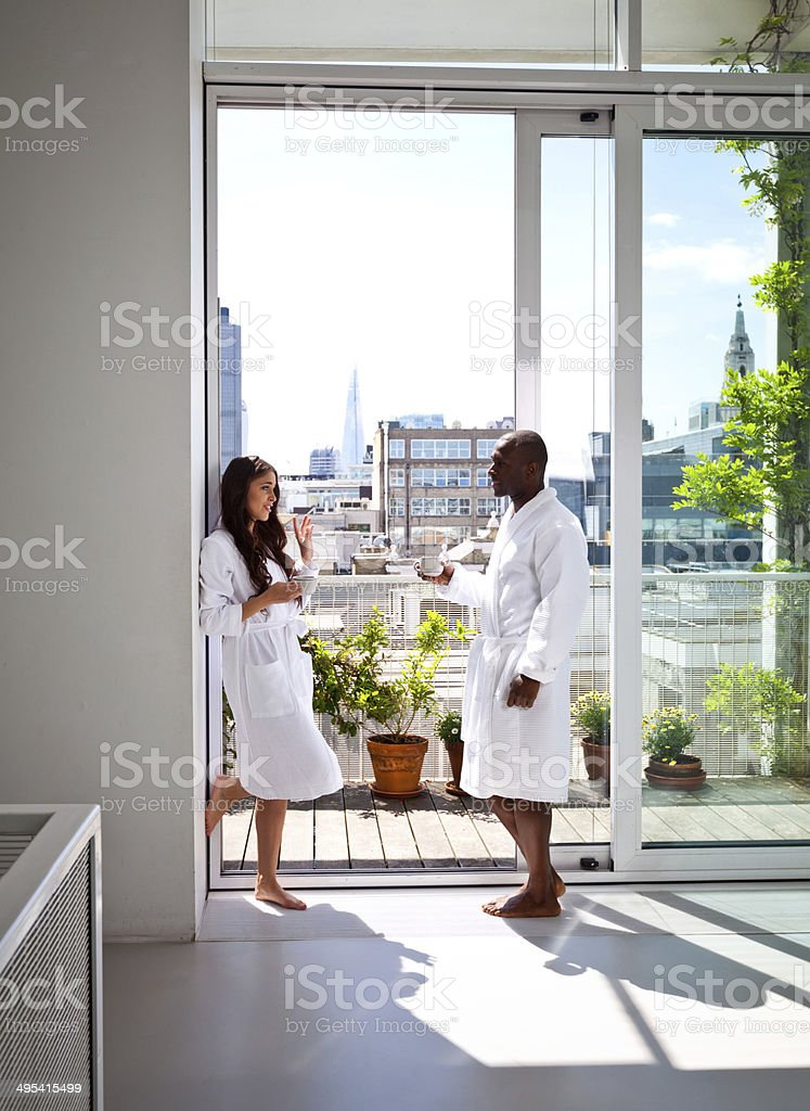 Couple in the morning Beautiful young woman and afro american man wearing white bathrobes talking with cup of coffee in their apartment in the morning. Adult Stock Photo