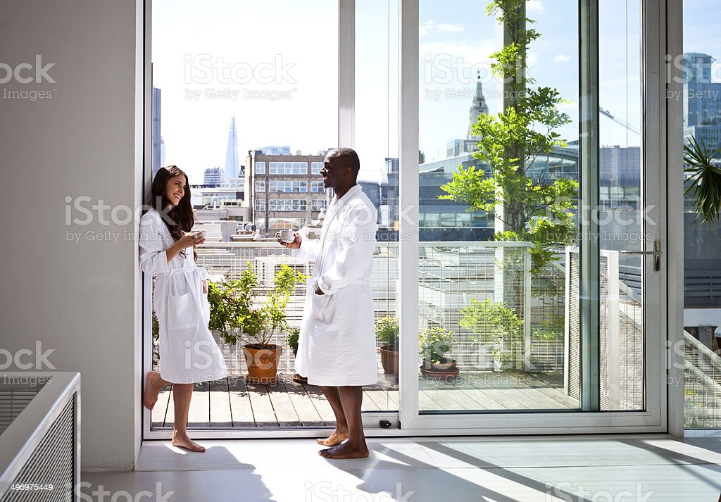 Couple in the morning Beautiful young woman and afro american man wearing white bathrobes standing with cup of coffee in their apartment in the morning. Adult Stock Photo