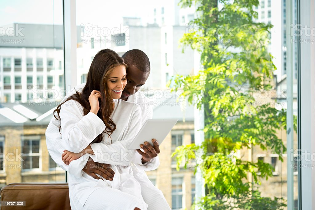 Couple in the morning Afro american man and beautiful brunette wearing white bathrobes using a digital tablet together in the morning. 30-39 Years Stock Photo