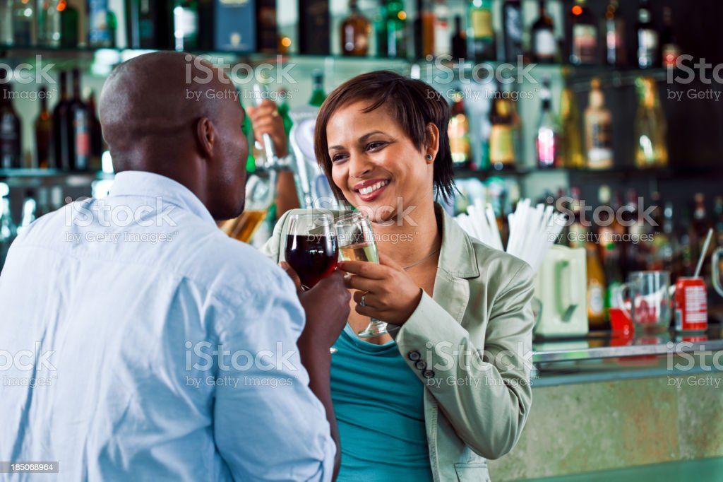 Couple in the pub Smiling young woman drinking wine with her partner in the pub. Adult Stock Photo