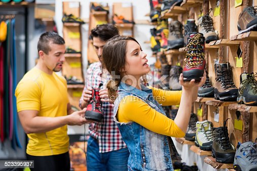 istock Couple in the store choosing hiking boots 523395937