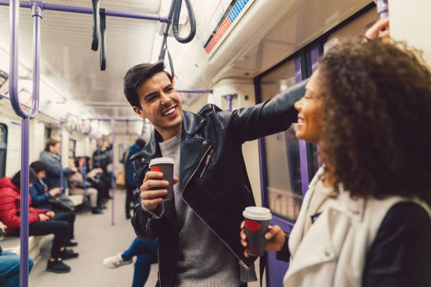 Couple in the subway train Young people talking and drinking coffee while travelling in the subway subway stock pictures, royalty-free photos & images