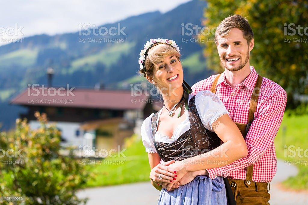 Paar in Tracht stehend auf Wiese in Alpen Berge – Foto