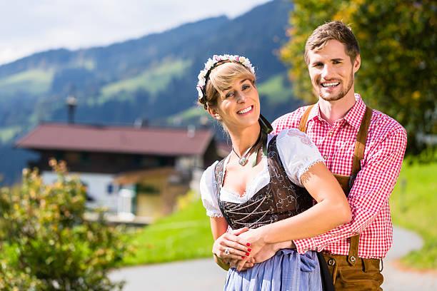 paar in tracht stehend auf wiese in alpen berge - bayerische tracht stock-fotos und bilder
