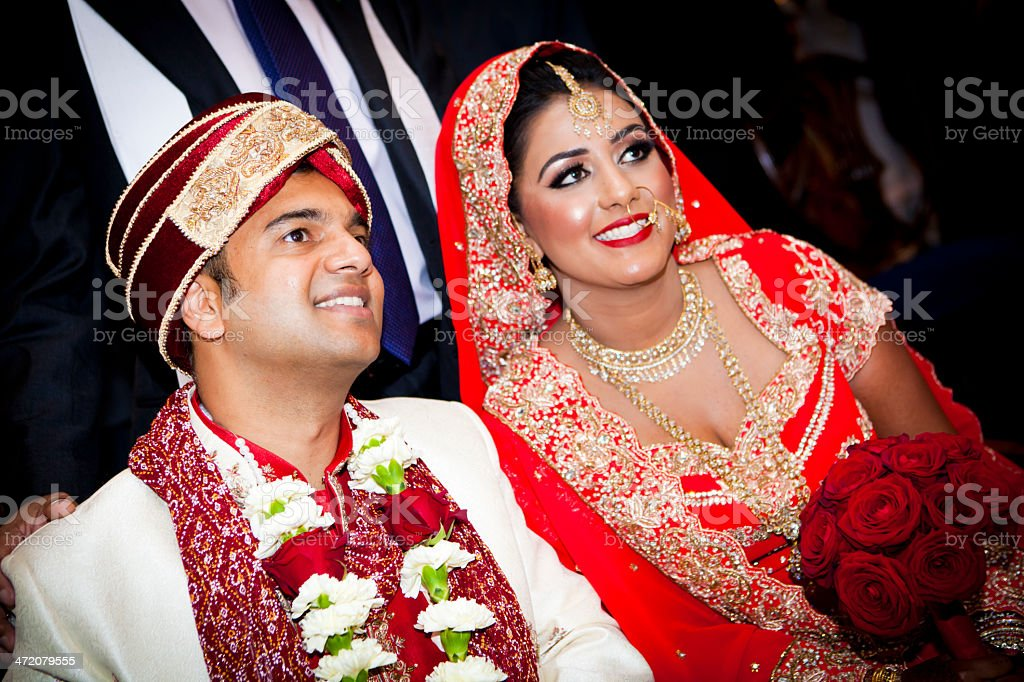 Couple in traditional Asian wedding outfits smiling stock photo