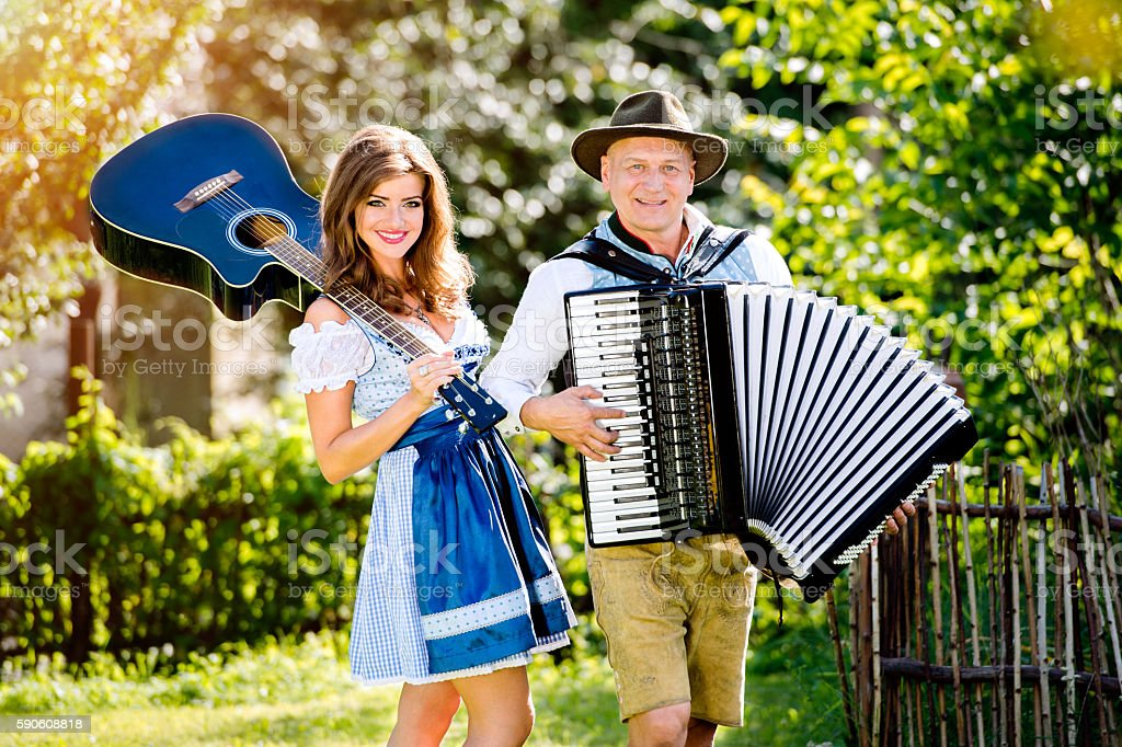 Couple in traditional bavarian clothes with guitar and accordion – Foto