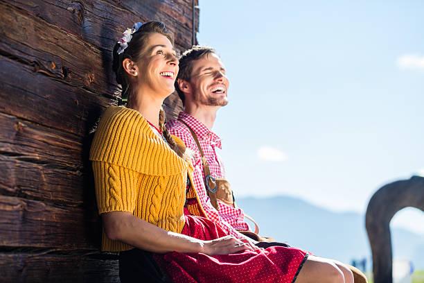 paar in traditioneller kleidung vor berghütte - bayerische tracht stock-fotos und bilder
