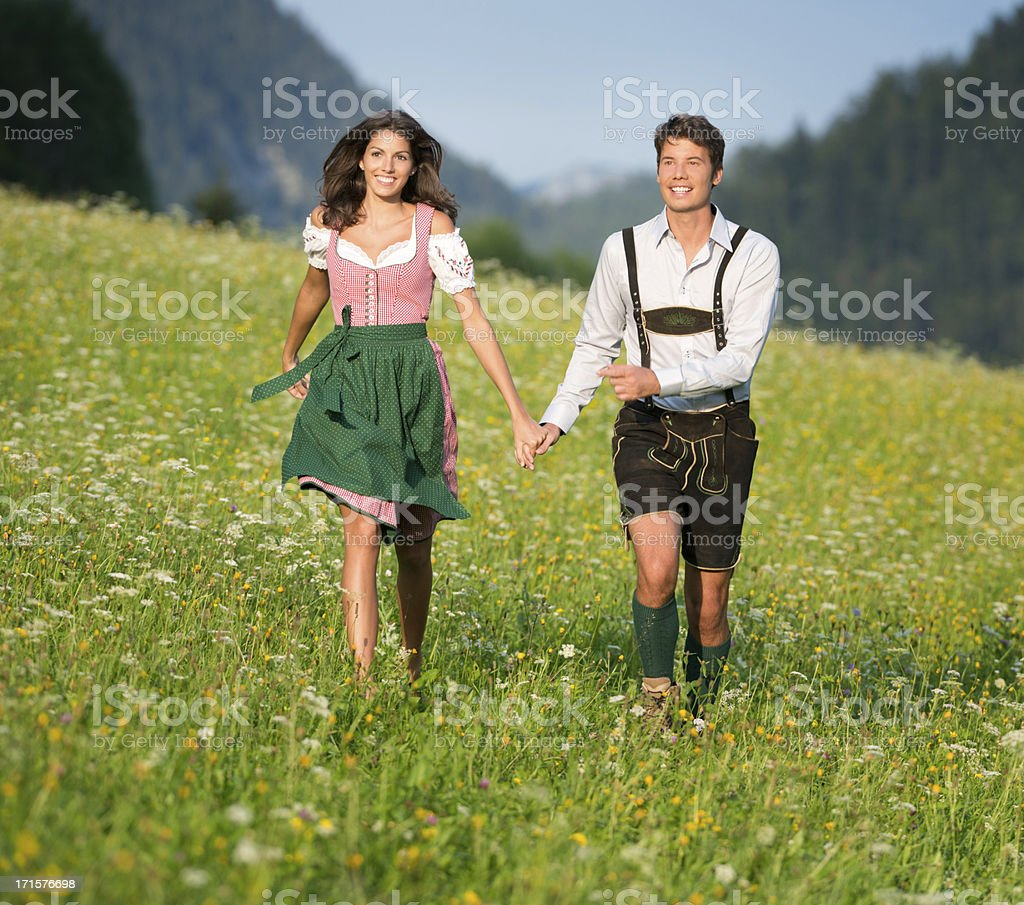 Couple in traditional Tracht running through the Meadows (XXXL) stock photo