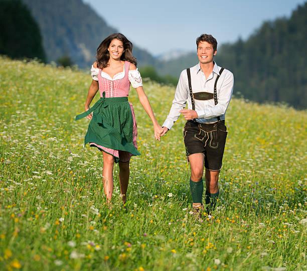 paar in traditioneller tracht laufen durch die meadows (xxxl) - bayerische tracht stock-fotos und bilder