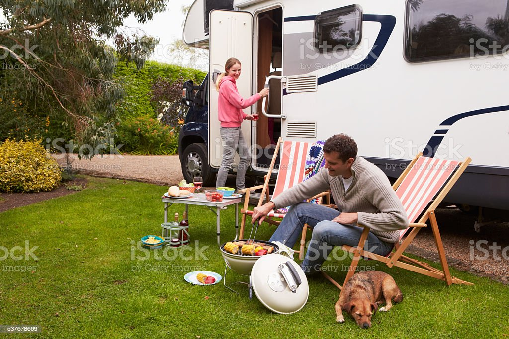 Couple In Van Enjoying Barbeque On Camping Holiday stock photo