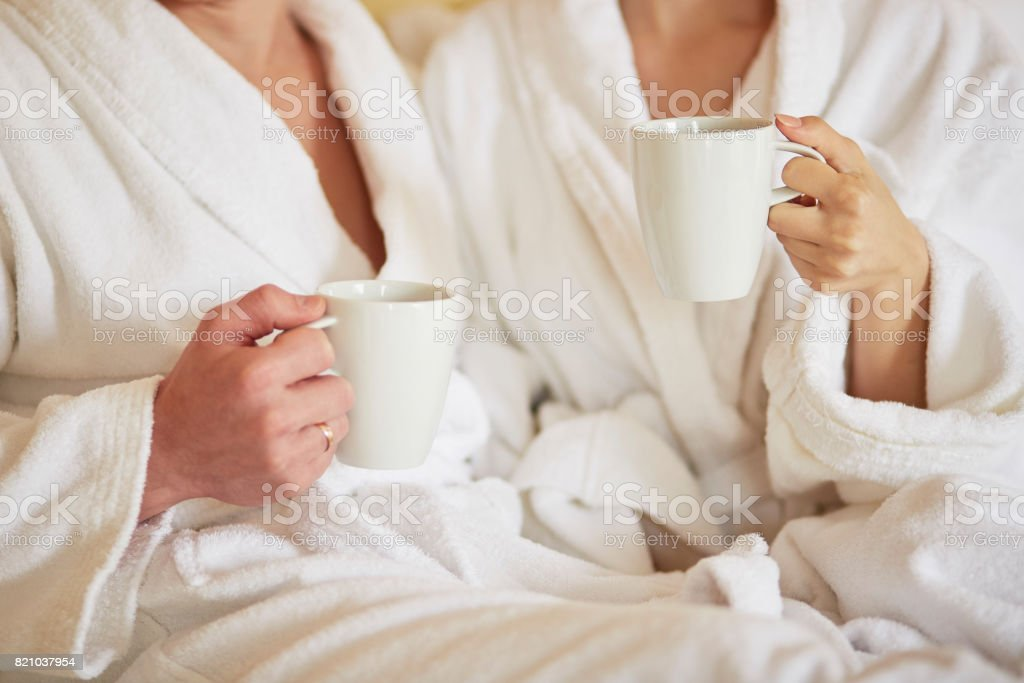 Couple in white bathrobes in bed, drinking coffee - foto stock