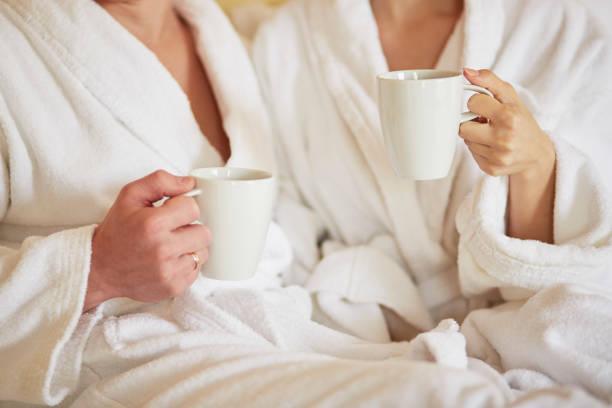 couple in white bathrobes in bed, drinking coffee - accappatoio foto e immagini stock