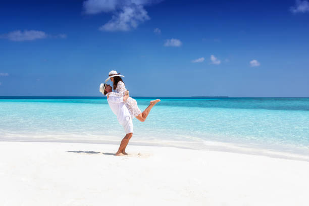 Couple in white summer clothes on a tropical beach stock photo