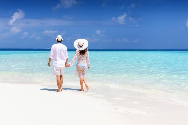 Paare in weißer Sommerkleidung spazieren an einem tropischen Strand entlang – Foto