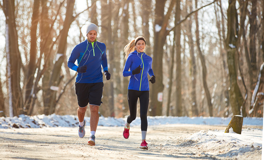Couple in winter running together in nature