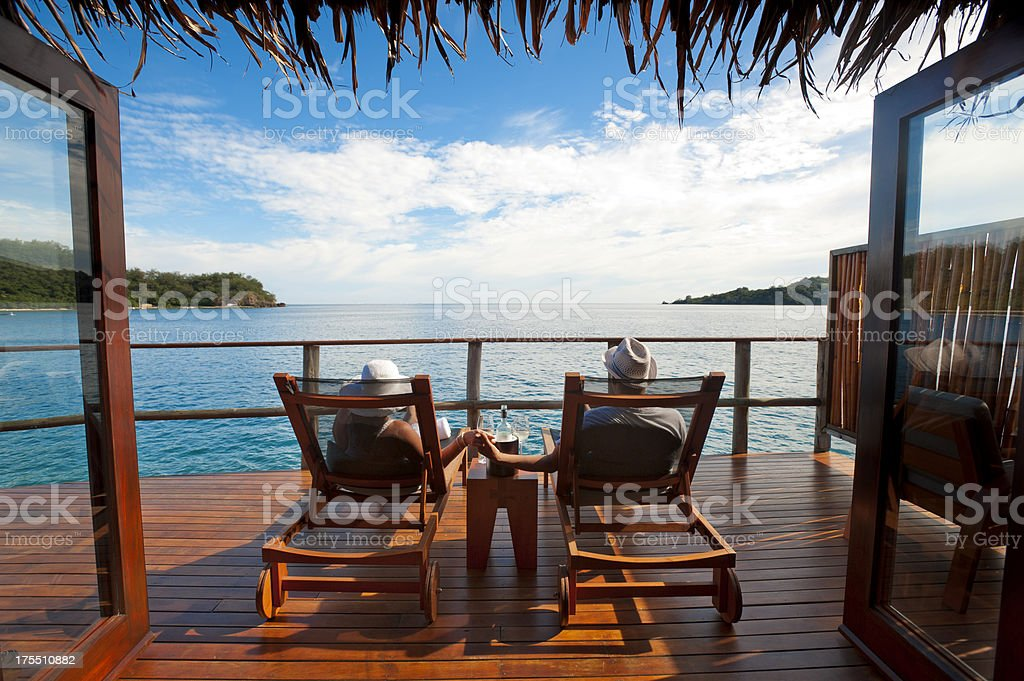 Couple in wood lawn chairs staring at water royalty-free stock photo