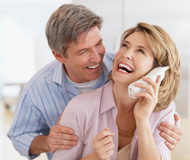 Couple indoors with a telephone laughing  cordless phone stock pictures, royalty-free photos & images