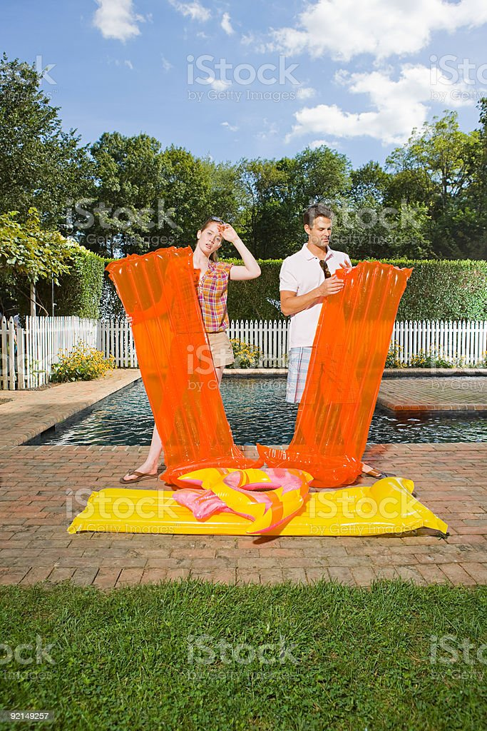 Couple inflating air mattresses royalty-free stock photo