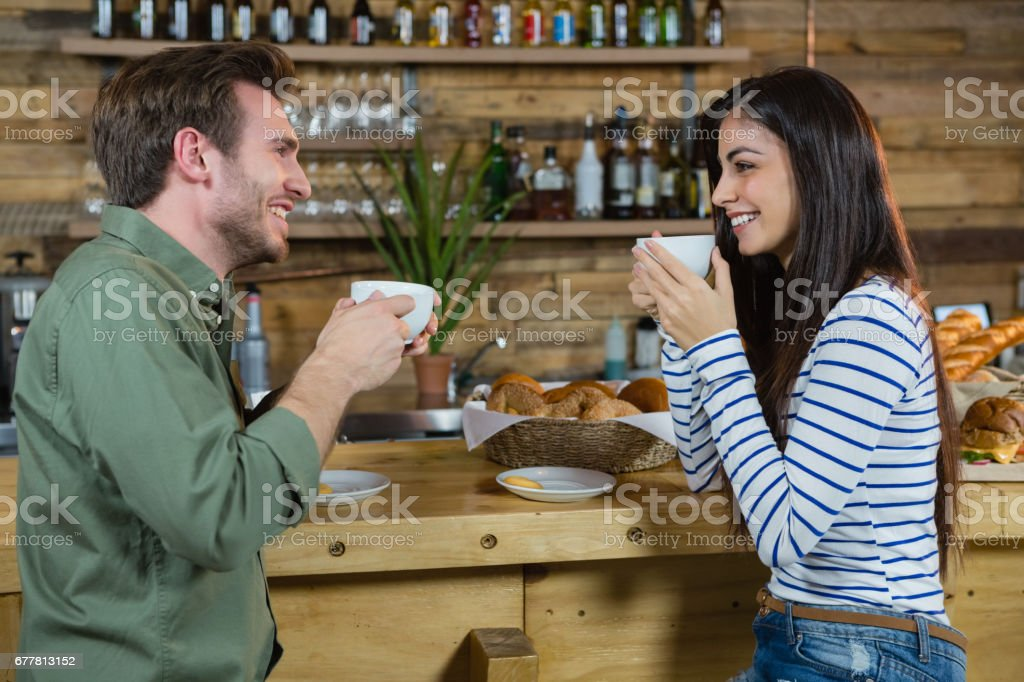 Couple interacting each other while having coffee at counter royalty-free stock photo