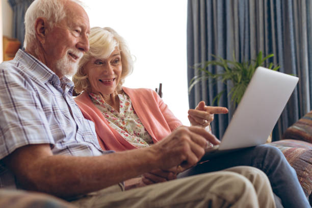 Couple interacting with each other while using laptop stock photo