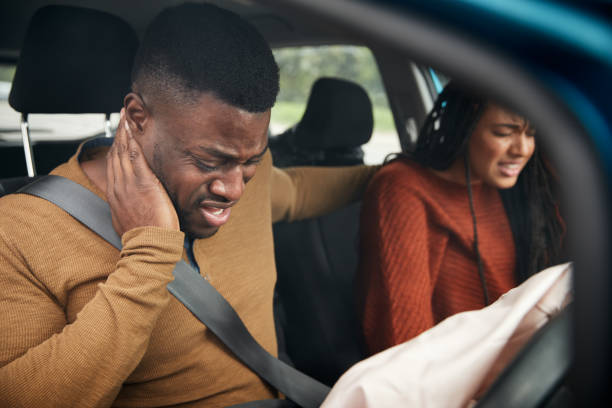 Couple Involved In Car Crash With Male Driver Suffering With Whiplash Injury Couple Involved In Car Crash With Male Driver Suffering With Whiplash Injury passenger stock pictures, royalty-free photos & images