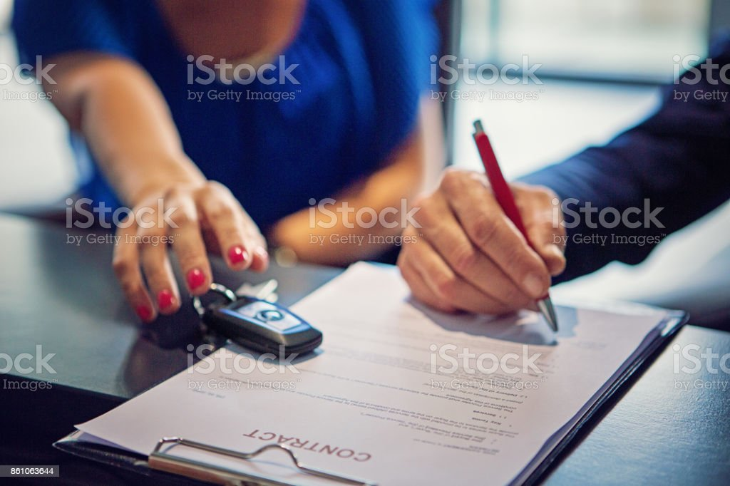 Couple is buying new car and signing the contract stock photo