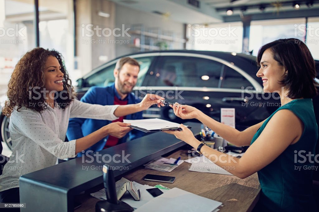 Couple is buying new car and signing the contract royalty-free stock photo