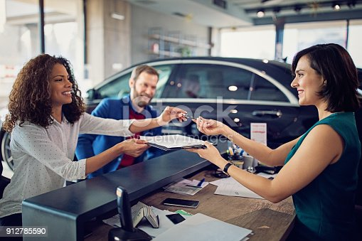 Couple is buying new car and signing the contract