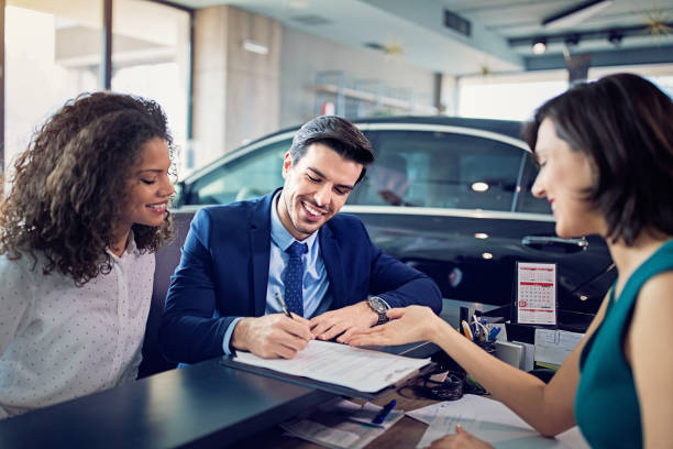Couple is buying/lease new car and signing the contract stock photo