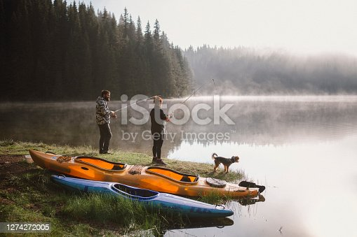 Couple is fishing next to the lake while on camping vacation