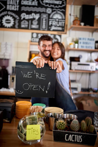 Couple is holding a sign we're open stock photo