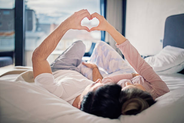 Couple is lying on the bed and making heart with their hands stock photo