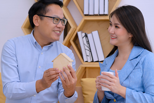 couple is planing for saving. They put coin into coin bank. Financial and saving concept.
