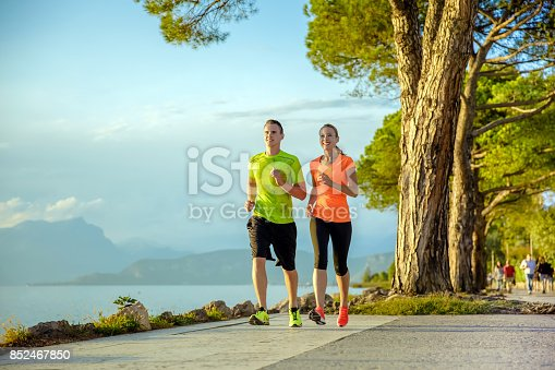 Young sexy couple is running along the promenade. they are doing their sport workout in the beautiful sundown along the beach. colorful dress, trees, water, mountains and a amazing blue sky.