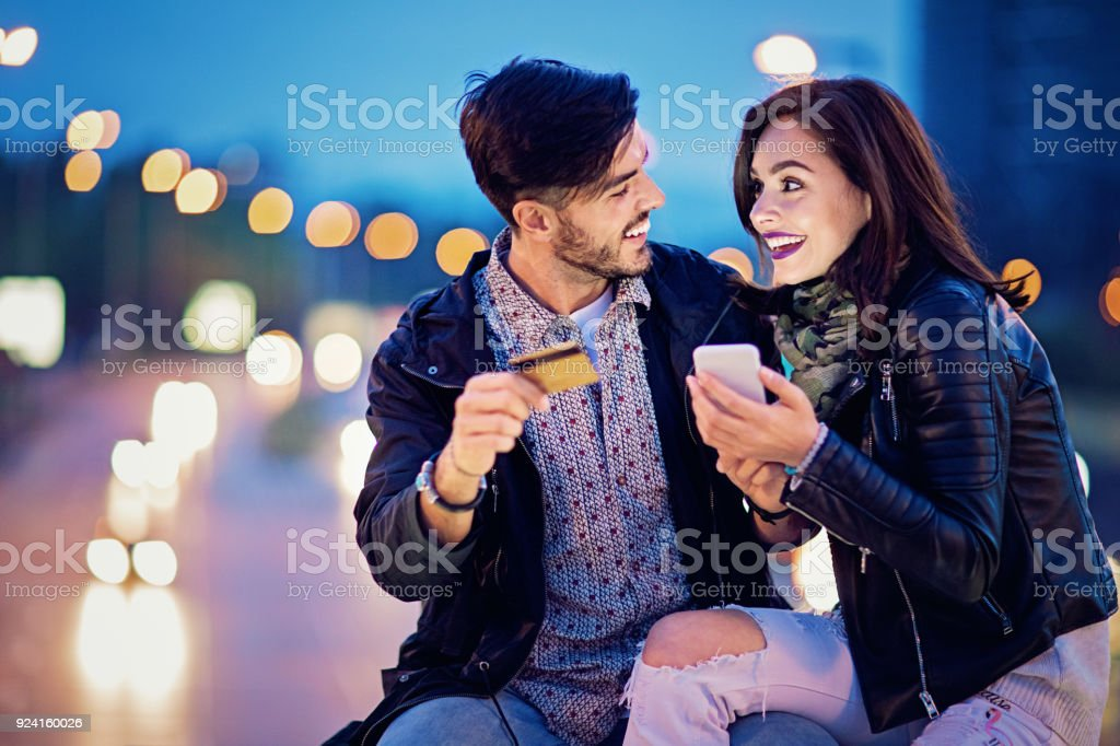 Couple is shopping online on the bridge in the night stock photo