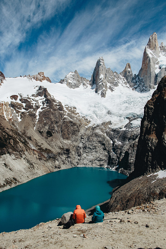Couple is sitting and looking at the scenic view of Laguna Sucia and Cerro Torre in Patagonia, Argentina