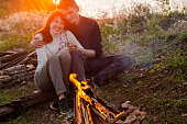 A couple is sitting by the fire, hugging each other