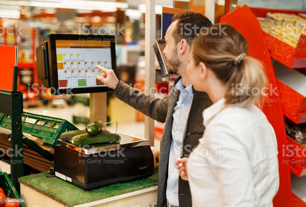 Couple is standing with fruit near weigher in supermarket stock photo