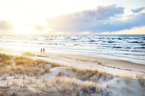 A couple is walking through the Baltic sea shore at sunset. Sand dunes and plants close-up. Colorful evening clouds. Waves and water splashes. Idyllic seascape. Latvia
