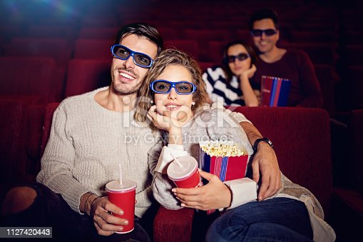 187095683 istock photo Couple is watching 3D movie in the cinema theater 1127420443