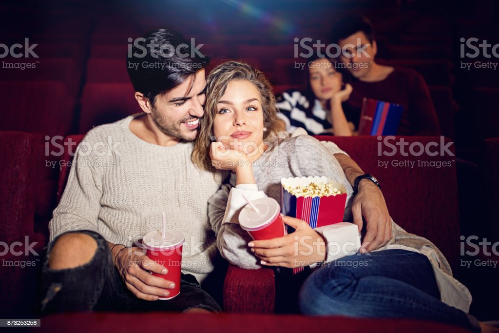 Couple is watching romantic movie in the cinema theater stock photo