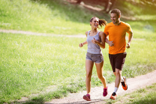couple jogging and running outdoors in nature - jogging stock pictures, royalty-free photos & images