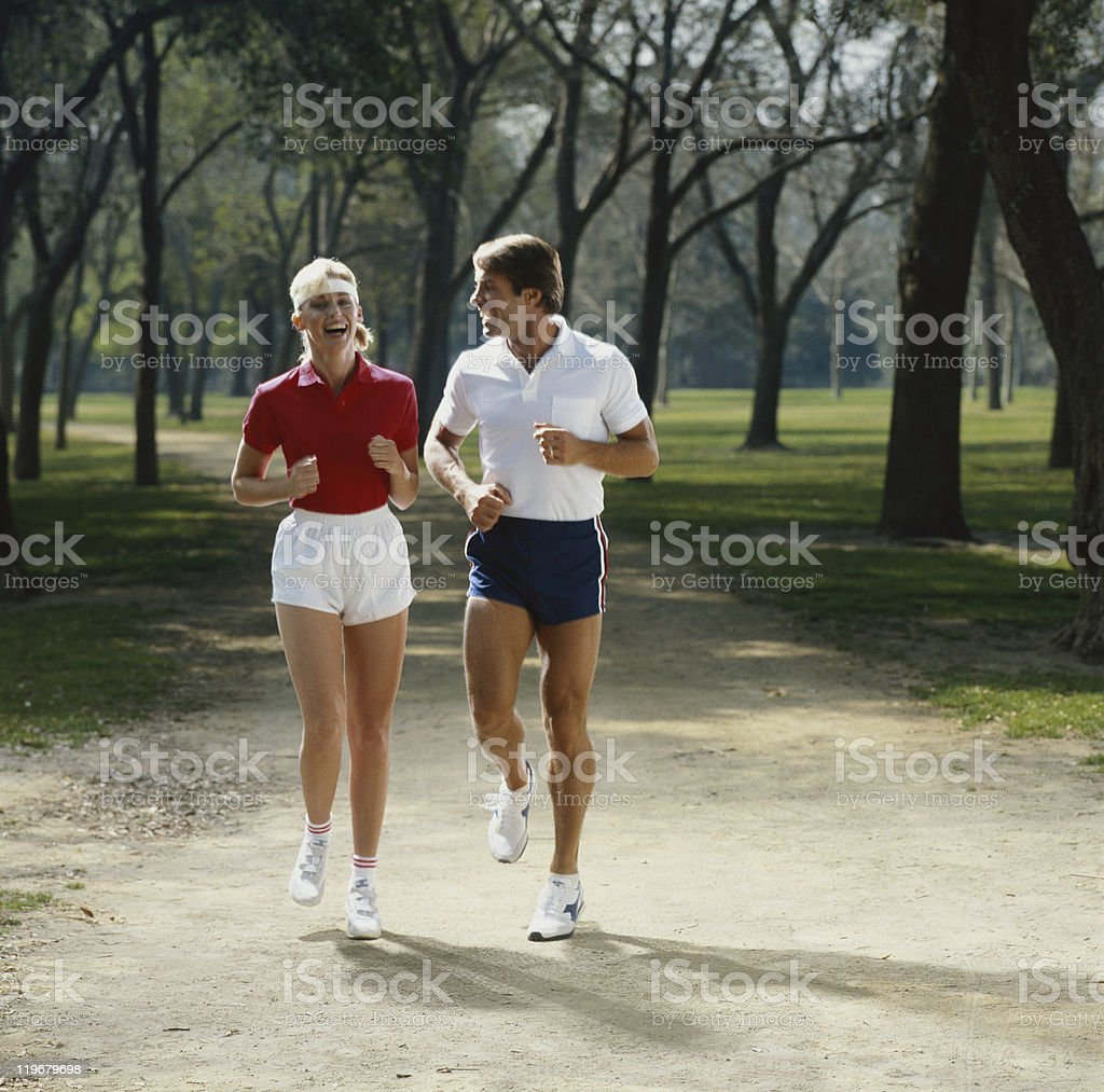 Casal jogging no parque, sorrindo - foto de acervo