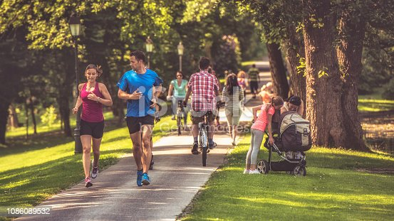 Couple jogging through a busy park on a sunny day. People cycling and walking and a woman and girl looking at a baby in a baby carriage.