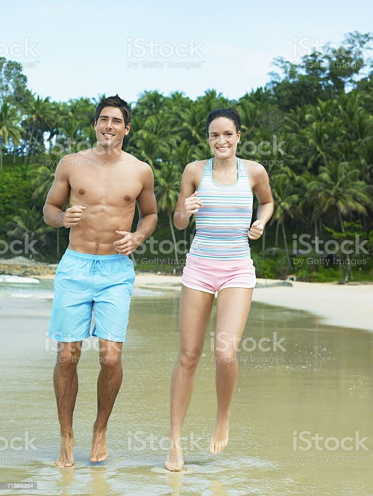 Couple jogging on beach royalty-free stock photo