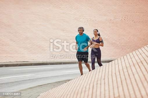 Couple running on street. Determined man and woman jogging together against wall. They are in sports clothing at city.