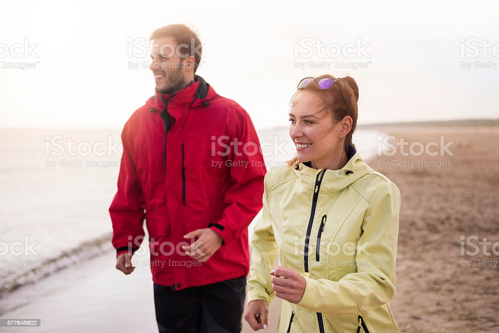Couple jogging on the beach in cold weather stock photo