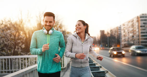 couple jogging outdoors - jogging stock pictures, royalty-free photos & images
