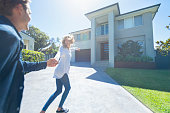 Couple joyfully running into their new home. They are both wearing casual clothes, very happy and smiling. The house is contemporary double brick with render, driveway and balcony. They are holding hands.